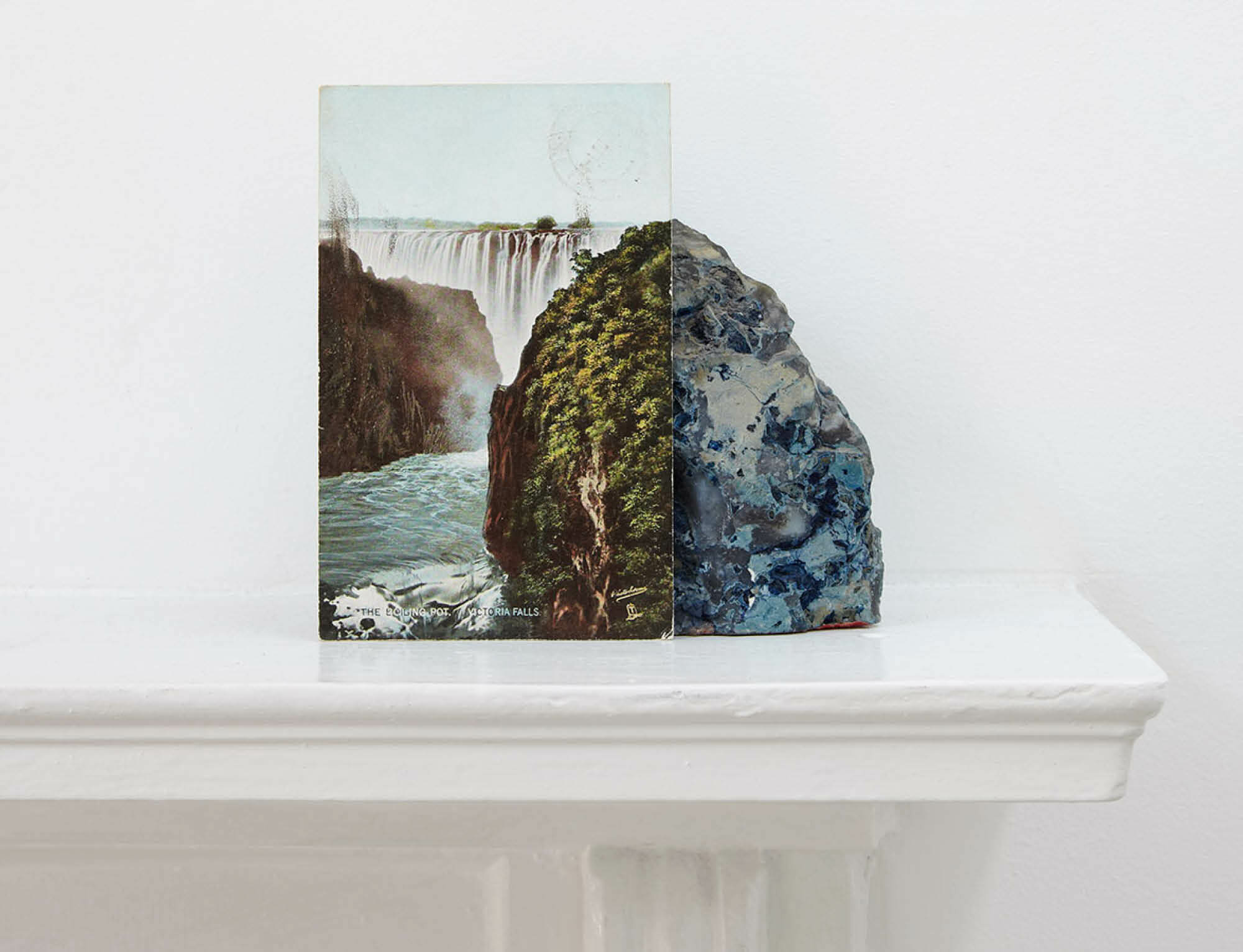 Image: Stuart Whipps, A postcard of Victoria Falls leaning against a geological sample from John Latham's mantlepiece, C-Print, 31.25cm x 25cm, 2013 (John Latham at 100: African Incidentalism 0)